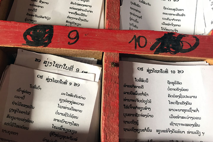 Fortune sticks, poetry and boxes of paper notes in Lao Buddhist temples